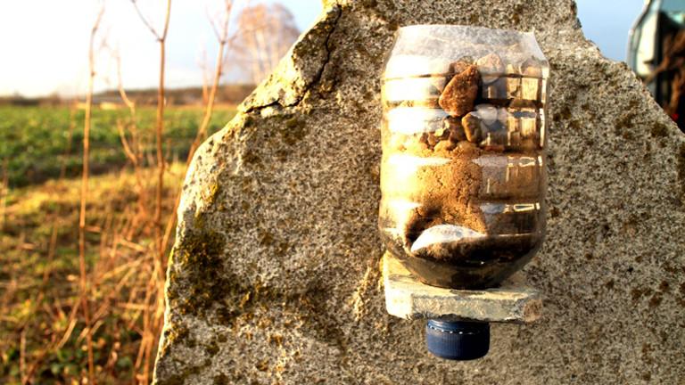 Flasche, gefüllt mit Sand und Kies