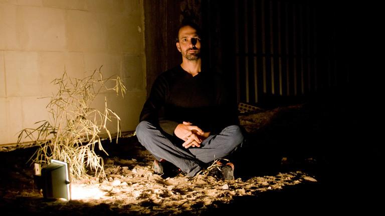 Mann sitzt in einer dunklen Ecke