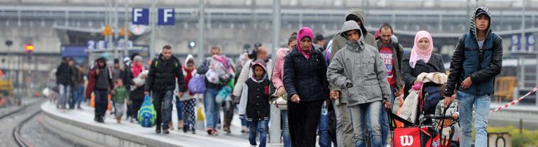 Flüchtlinge gehen am 07.10.2015 über einen Bahnsteig auf dem Bahnhof in Passau (Bayern). Sie waren mit einem Zug aus Österreich gekommen und mussten in Passau den Zug verlassen, um sich vor der Weiterreise registrieren zu lassen.