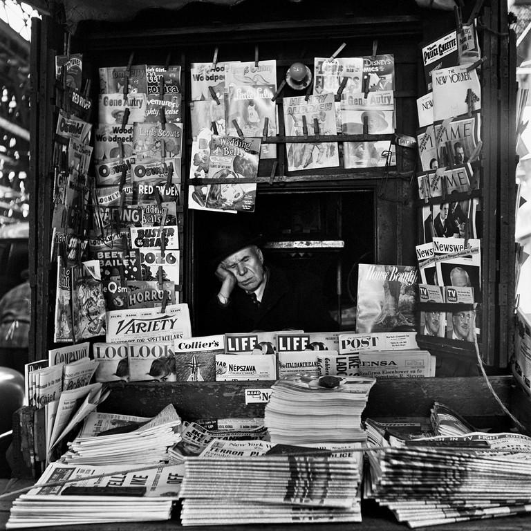 Ein MAnn in einem Zeitungskiosk, schwarz-weiß Fotografie von Vivian Maier.