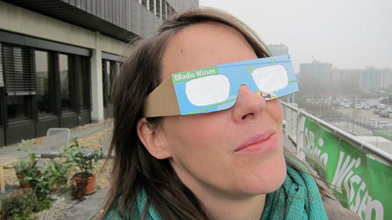 Sonnenfinsternis-Brille mit DRadio Wissen-Logo, eine Frau blickt in den Himmel