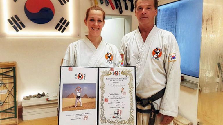Caro steht mit einer Urkunde in der Hand neben ihrem Taekwondolehrer.
