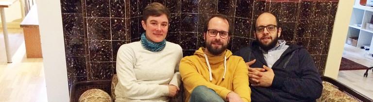 Reporter Dominik Peters auf einem Sofa mit Lena (links) und Imad (rechts)