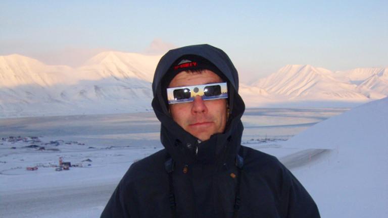 Mann mit Sonnenfinsternisbrille vor Schneelandschaft