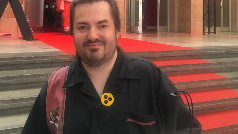 Tim ist 37 Jahre alt, trägt einen langen braunen Zopf und ein schwarzes Hemd. Auf der Vorderseite trägt Tim ein kleines rundes Blindenabzeichen.