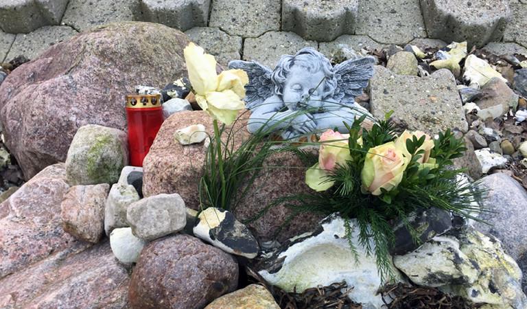 Blumen, eine Kerze und ein Engel am Strand von Bülk
