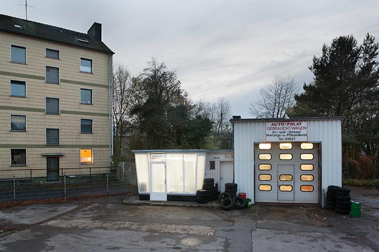Hinterhof mit Wellblech-Garage und kleinem Tankstellen-Häuschen