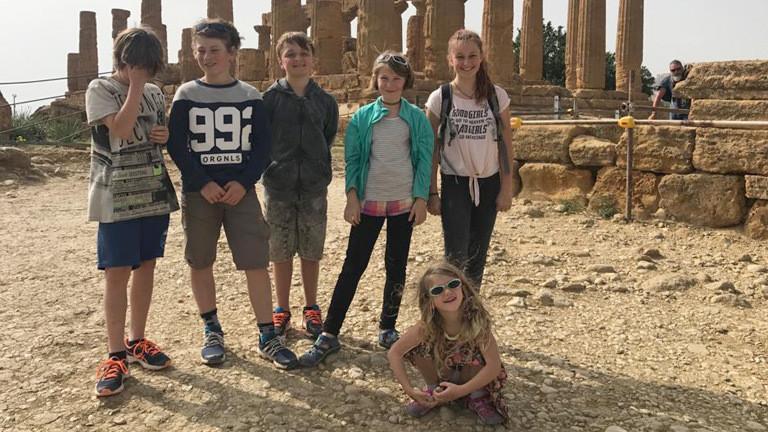 Antike Säulen. Im Vordergrund sechs Kinder.