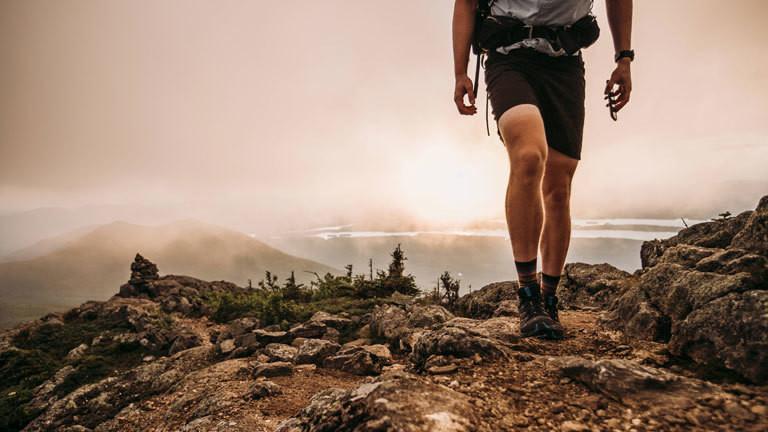 Ein Mann wandert mit seinem Smartphone in der Hand über einen einsamen Gipfel.