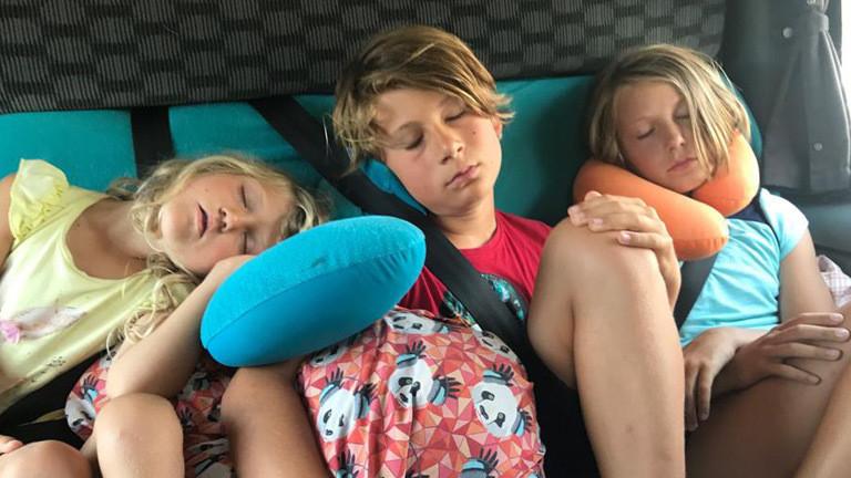 Liv, Paul und Fannie sitzen auf der Rückbank eines Bullis während sie mit ihren Eltern Europa durchqueren.