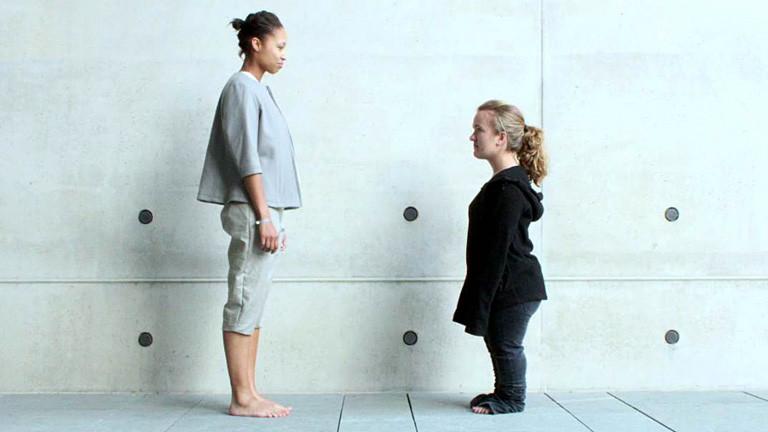 Eine groß gewachsene Frau und eine Kleinwüchsige stehen sich gegenüber.