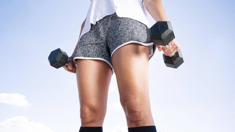 Training mit Hanteln: Eine junge Frau in Shorts trainiert.