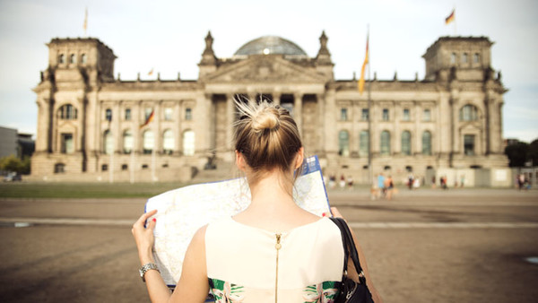 Junge Frau mit Stadtplan vorm Berliner Reichstag
