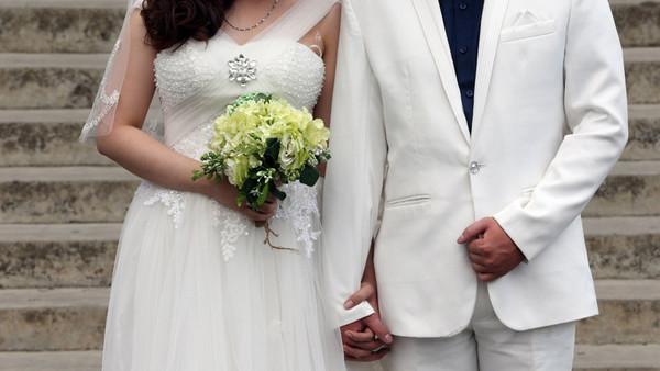 Ein Hochzeitspaar in weißer Kleidung.