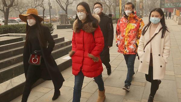 Junge Chinesen gehen mit Atemmasken eine Straße lang.