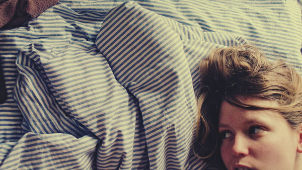 Frau liegt im Bett.
