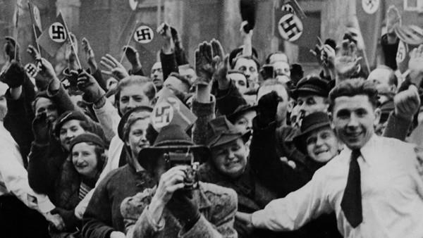 Menschen freuen sich bei der Ankunft von Rudolf Hess. Manche zeigen den Hitlergruß andere schwenken Hakenkreuz-Flaggen.