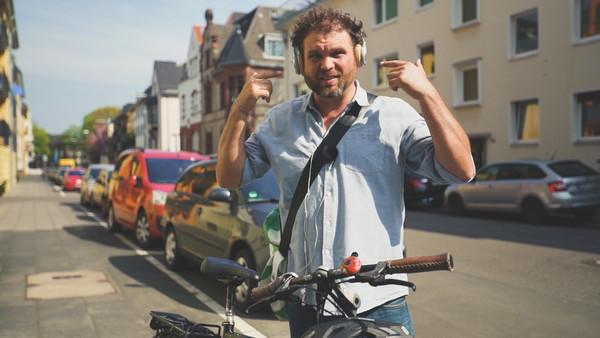 Moderator Paulus Müller auf einer Straße mit seinem Fahrrad. Auf den Ohren hat er Kopfhörer und es stellt sich die Frage, ob das erlaubt ist.
