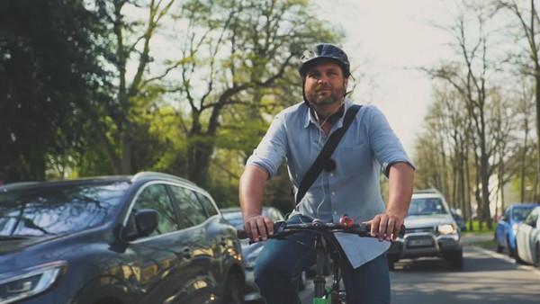 Deutschlandfunk-Nova-Reporter Paulus Müller fährt mit einem Fahrrad durch eine Straße und trägt einen Helm.