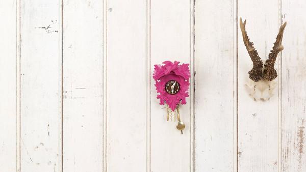 Geweih und Kuckucksuhr hängen an einer Wand.