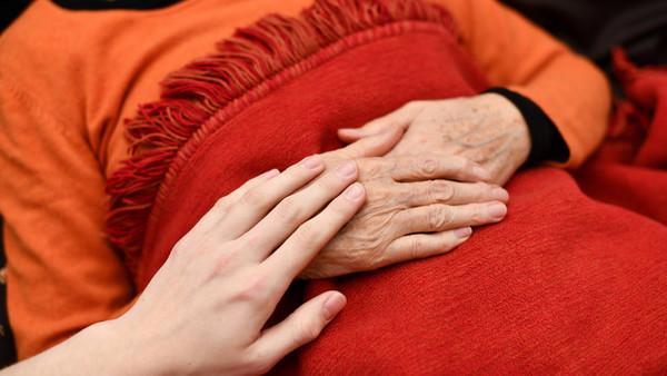 Eine jüngere Person hält einer älteren, kranken Person die Hand.