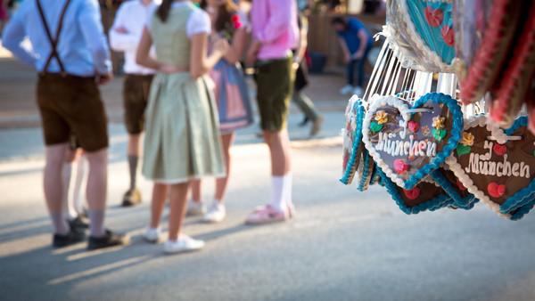 """Menschen in Dirndl und Lederhose auf dem Oktoberfest, im Vordergrund Lebkuchenherzen, auf denen """"München"""" steht."""