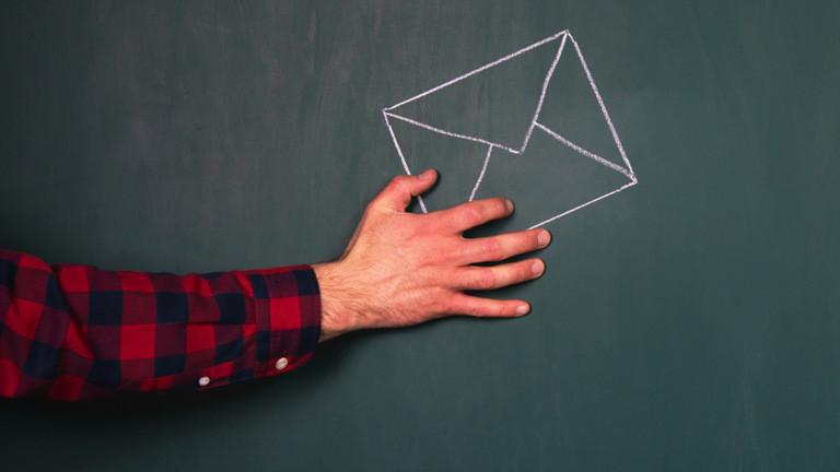 Ein Mann hält einen Brief in der Hand, der an eine Tafel gezeichnet wurde.
