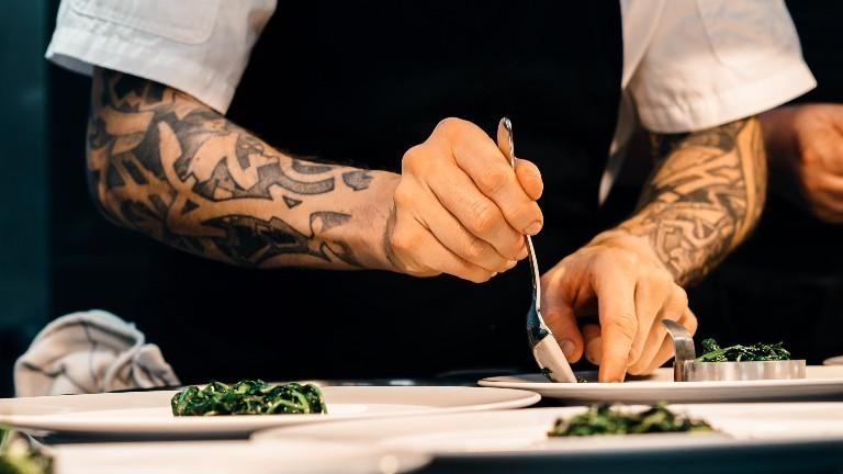 Ein Koch in einem Restaurant richtet ein Gericht an.