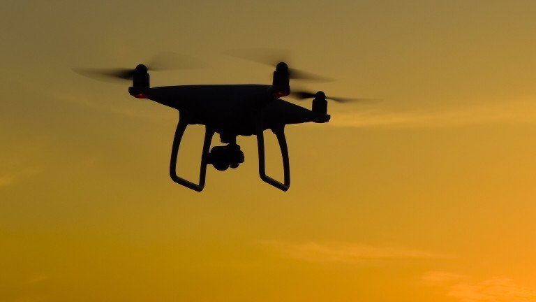 Eine Quadrocopter-Drohne fliegt am Himmel.