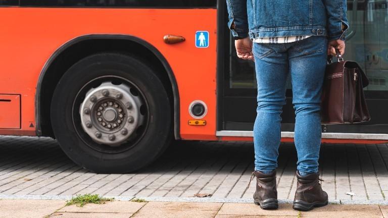 Eine Mann steht vor einer Bustür.