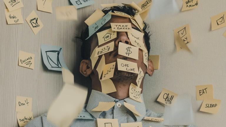 Das Gesicht eines Mannes ist mit vielen Zetteln beklebt, während er an einer Wand lehnt.