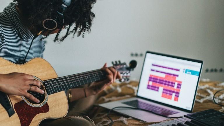 Eine Musikerin sitzt auf ihrem Bett, spielt Gitarre und nimmt sich dabei auf.