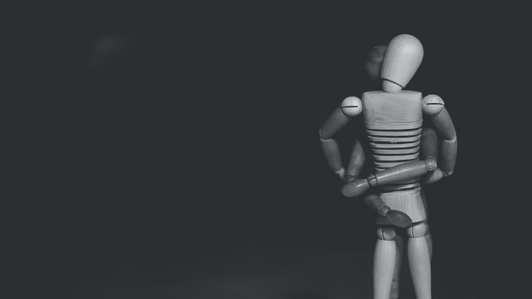 Zwei Holzfiguren umarmen sich