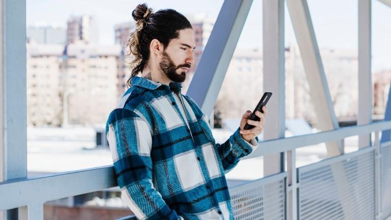 Ein Mann lehnt an einer Brücke und schaut auf sein Smartphone.