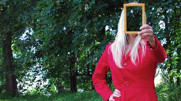 Frau hält Bilderrahmen vor ihr Gesicht