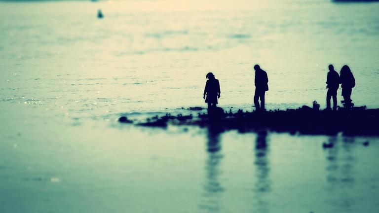 Menschen stehen am Flussufer
