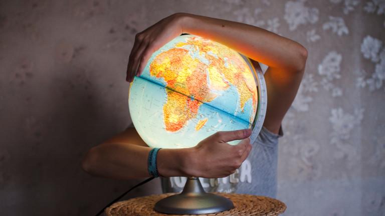 Ein Mann umarmt eine beleuchteten Globus