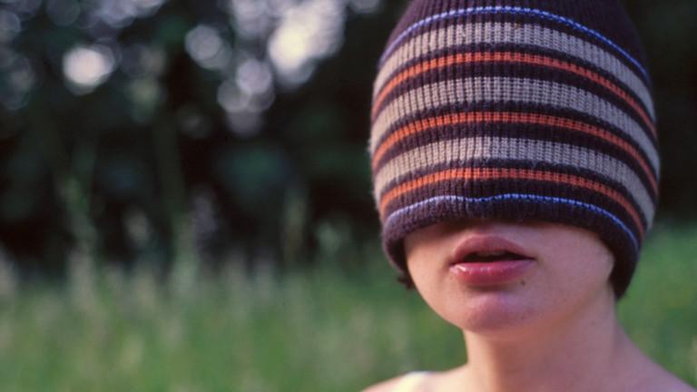 Eine junge Frau hat eine Mütze bis über die Nase gezogen. Sie kann nichts sehen.
