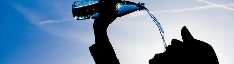 Ein Mann schüttet Wasser aus einer Flasche direkt in den Mund.