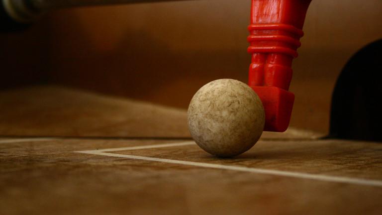 Eine Kickerfigur berührt einen Spielball.