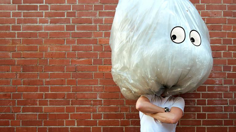 Ein Mann steht vor einer roten Backsteinwand. Auf seinem Kopf ist eine große Tüte, die ausgestopft ist, darauf sind zwei Augen angebracht.