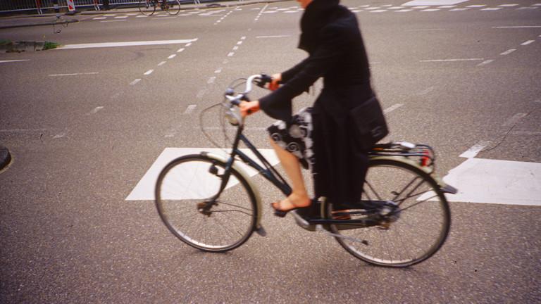 Eine Frau fährt auf der Straße Fahrrad.