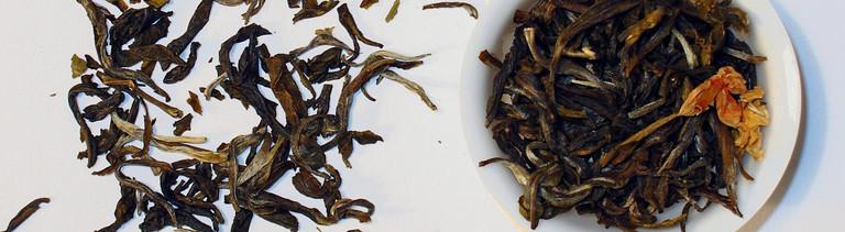 In einer weißen kleinen Schale ist loser Tee. Links daneben liegt mehr loser Tee.