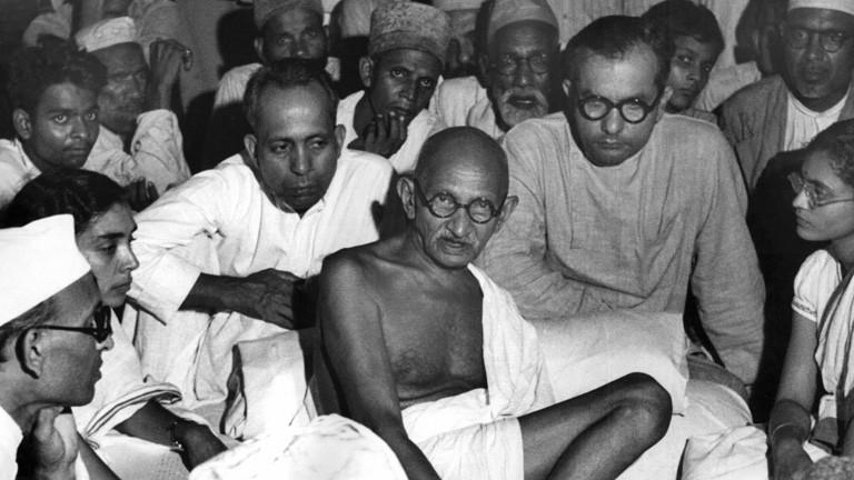 Schwarz-Weiß-Foto. Mahatma Gandhi sitzt zwischen Muslimen, die ihm zuhören.