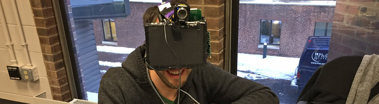 Reporter Thomas Reintjes trägt die Brille Brand Killer. Vor seinen Augen trägt er einen kleinen Flachbildschirm, darüber sitzt eine Webcam.