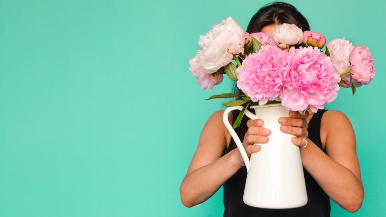 Eine Frau hält eine Vase mit Blumenstrauss vor ihr Gesicht.