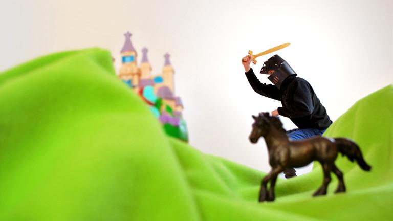 Surreales Bild mit Ritter und Spielzeugpferd und Schloss