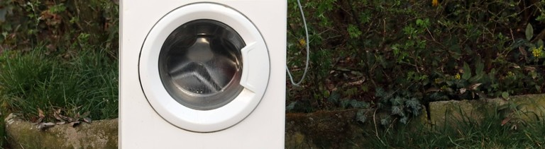 Eine gebrauchte Waschmaschine steht am Wegesrand.