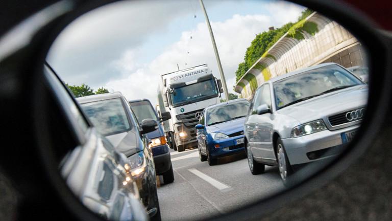 Im Seitenspiegel des Autos zeigt sich ein langer Stau auf der Autobahn.
