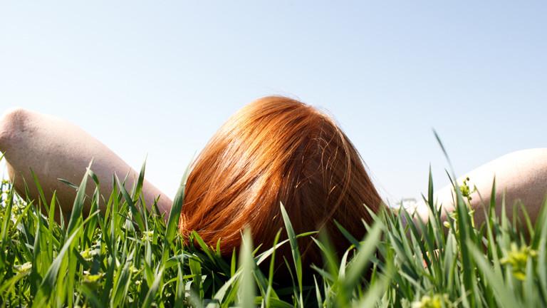 Eine junge Frau mit roten Haaren liegt in der Wiese.
